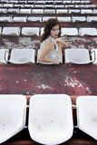 Retro girl sitting in stadium Royalty Free Stock Images