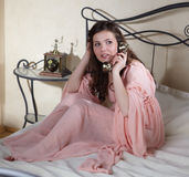 Retro girl talking by phone Stock Images