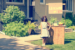 Retro girl wearing sunglasses with lemonade stand. In the front yard Royalty Free Stock Photo