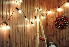 Retro- Girlande von glühenden Birnen auf einer hölzernen Wand Drei Weihnachtskugeln getrennt auf Weiß Lizenzfreie Stockbilder