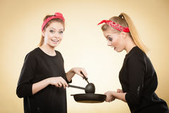 Retro girls cooking and frying on pan. Stock Photography