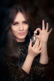 Retro glamour woman holding vintage perfume bottle Stock Photos