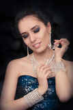 Retro glamour woman holding vintage perfume bottle wearing silver accessories. Glamorous portrait of a beautiful young woman preparing for party using a vintage Stock Image