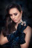 Retro glamour woman holding vintage perfume bottle wearing silver accessories. Glamorous portrait of a beautiful young woman preparing for party using a vintage Stock Photography