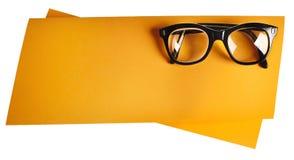 Retro glasögon med den svarta ramen på orange idérik service Arkivbilder