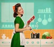 Retro glimlachende vrouw die en receptenboek in haar kitch koken lezen stock afbeeldingen