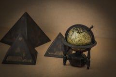 Retro globe model and pyramids Stock Image