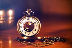 Retro gold pocket watch in beautiful  candle light on brown back Stock Photo