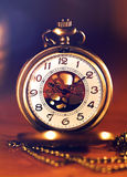 Retro gold pocket watch in beautiful light candle on brown background Royalty Free Stock Images