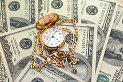 Retro golden pocket watch on Hundred Dollars. Stock Images