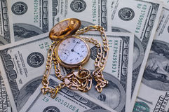 Retro golden pocket watch on Hundred Dollars. Stock Photos