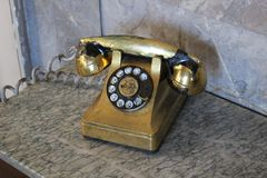Retro- goldenes Telefon auf dem Tisch lizenzfreies stockbild