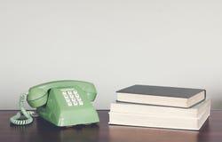 Retro- grünes Telefon auf hölzerner Tabelle mit Buchweinleseton lizenzfreies stockfoto