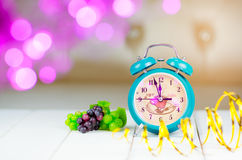 Retro green alarm clock with five minutes to midnight. Stock Photography