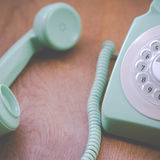Retro Green Rotary Dial Phone. Retro Filtered Dial Telephone Closeup With Wooden Background Royalty Free Stock Photography