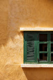 Retro green Window with Open Wooden Shutters on yellow wall texture. Royalty Free Stock Photo
