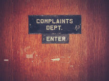 Retro Grunge Complaints Dept Door. Retro Filtered Image Of A Grungy Complaints Department Sign On A Door Royalty Free Stock Image