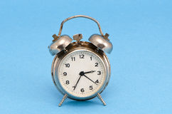 Retro grunge rusty alarm clock blue background Royalty Free Stock Photo