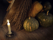 Retro grunge still life with with broom stick, candle and pumpkins. Retro grunge still life with broom, candle and pumpkins by staircase. Occult or esoteric Royalty Free Stock Photo