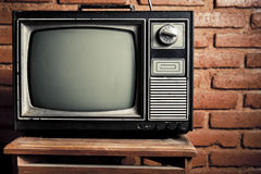 Retro grunge tv against brick wall. Retro tv turned of against brick wall Royalty Free Stock Photos