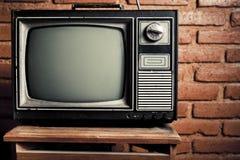 Retro grungeTV tegen bakstenen muur. Royalty-vrije Stock Foto's