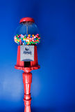 Retro Gumball Machine. An old fashioned gumball machine against a colorful blue background, vertical royalty free stock photo