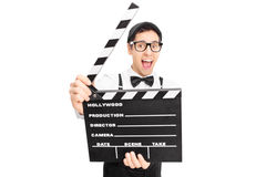 Retro guy posing behind a movie clapperboard Royalty Free Stock Photography