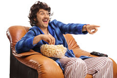 Retro guy seated in an armchair watching television and laughing Stock Images
