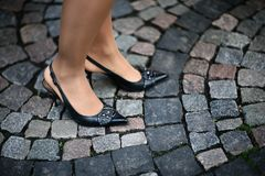 Retro high hills. Female feet in high hills shoes standing on cobbled road Royalty Free Stock Images