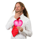 Retro hippie man holding love heart thinking. Portrait of a hippie man in large retro red tie holding a love heart and looking up thinking royalty free stock photo