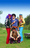 Retro hippie party group. Retro theme party group dress up, background of park and greenery with gradient blue sky. Three men and a lady wearing funky colourful stock photos