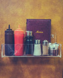 Retro Hipster Diner Detail. Retro Hipster Diner Or Dafe Menu And Condiments Against Faux Leather Backdrop Royalty Free Stock Image
