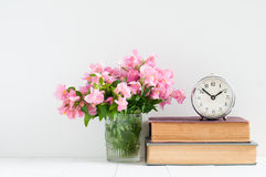 Retro home decor. A stack of books, flowers and a vintage alarm clock on a white wall shelf Stock Image