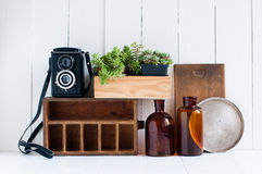 Retro home decor. Vintage home decor: old wooden boxes, houseplants, camera and old brown glass bottles on white wooden board, retro home interior Royalty Free Stock Photo