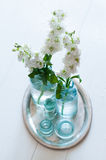 Retro home decoration. White matthiola flowers in vintage glass bottles vases in an antique silver tray on wooden floor, home decoration, interior details royalty free stock image
