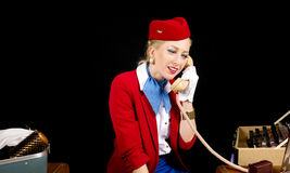 Retro hostess Preparing per lavoro e parlare di linea aerea su T fotografia stock libera da diritti