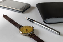 Retro hours against the background of modern phone. Still life with a retro for hours against the background of modern phone, a fountain pen and a purse Royalty Free Stock Photos