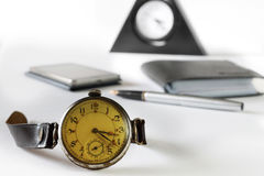 Retro hours against the background of modern phone. Still life with a retro for hours against the background of modern phone, a fountain pen and a purse Stock Images