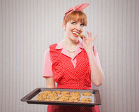 Retro housewife sneaking cookies Stock Photos