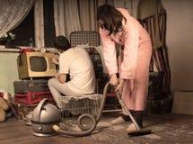 Retro huisvrouw die een slordige woonkamer schoonmaken Stock Foto's