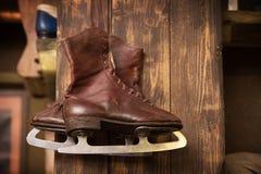 Retro ice skates, brown on wood wall Stock Photo