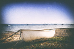 Retro image of a boat on a shingle beach. Retro 35mm film styled photograph of a boat on a shingle beach in Thorpe Bay Southend on Sea Essex. There is a chain stock photos