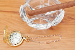 Retro image of gold pocket watch and a Havana cigar . Stock Photos