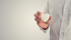 Retro image of a man holding a white heart Royalty Free Stock Image