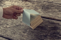 Retro image od male hand covering a house miniature made of wood Stock Photos