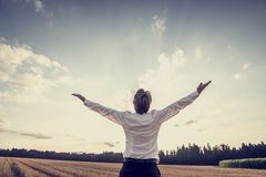 Retro image of victorious young businessman celebrating his success and achievement. By standing under majestic sky raising his arms in gratitude and royalty free stock photos