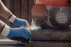 Retro image of workman using an angle grinder or circular saw to Royalty Free Stock Image