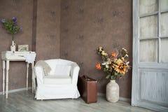 Retro- Innenraum mit einem Lehnsessel, Blumen, Tür und Koffer Lizenzfreies Stockfoto