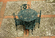 Retro iron garden furniture set on paved patio Stock Photo