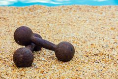 Dumbbells on the beach Royalty Free Stock Photography